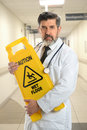 Hispanic doctor holding caution sign portrait of senior inside hospital Royalty Free Stock Photos