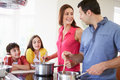 Hispanic family cooking meal at home together Royalty Free Stock Images