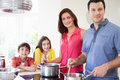 Hispanic family cooking meal at home together looking to camera Royalty Free Stock Photo