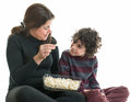 Hispanic family eating popcorn single mother sharing with her eight years old son latin enjoying the simplicity of life white Stock Image