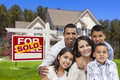 Hispanic family in front of sold real estate sign house happy their new and home for sale Royalty Free Stock Photography