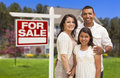 Hispanic family in front of their new home and sign mother father daughter with sold for sale real estate Royalty Free Stock Images