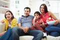 Hispanic family sitting on sofa watching tv together smiling away from camera Stock Image