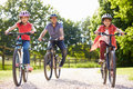 Hispanic father and children on cycle ride in countryside Royalty Free Stock Photos