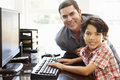 Hispanic father and son using computer at home Royalty Free Stock Photo