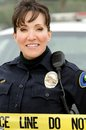 Hispanic female police officer smiling front her police car Stock Images