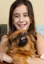 Hispanic girl carrying her small pekingese dog Royalty Free Stock Photo