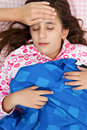 Hispanic girl sick with fever laying in her bed Stock Image
