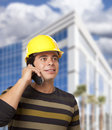 Hispanic Male Contractor on Phone in Front of Building Stock Images