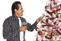 Hispanic man looking at a decorated christmas tree in dress shirt and tie holding drink while Stock Images