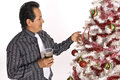 Hispanic man looking at a decorated christmas tree in dress shirt and tie holding drink while Royalty Free Stock Photos