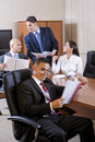 Hispanic man with report, colleagues conversing Stock Images
