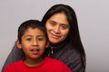 Hispanic mom and her child on gray background Stock Photo