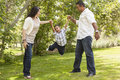 Hispanic Mother and Father Swinging Son in the Park Stock Images