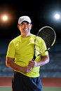 Hispanic senior tennis player portrait of holding raquet standing on court Stock Image