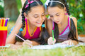 Hispanic sisters drawing in summer park happy Royalty Free Stock Images