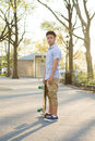 Hispanic skateboarder stands in the park looking far out over th photographed new york city Royalty Free Stock Image