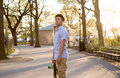 Hispanic skateboarder stands in the park looking far out over th photographed new york city Stock Photography