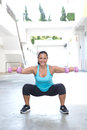 Hispanic sport woman doing squats with two pink dumbbell outdoor beautiful Stock Photography