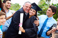 Hispanic student and family celebrating graduation hugging father whilst smiling at camera Stock Image