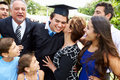 Hispanic student and family celebrating graduation outdoors smiling Stock Image