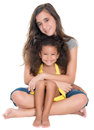 Hispanic teen hugs a little african-american girl Royalty Free Stock Photo