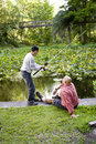 Hispanic teenager and father fishing in pond Royalty Free Stock Photo
