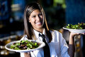 Hispanic waitress in restaurant serving salads Royalty Free Stock Photo