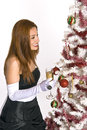 Hispanic woman looking at a decorated christmas tree in an evening gown and white gloves holding drink while Stock Photography