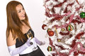 Hispanic woman looking at a decorated christmas tree in an evening gown and white gloves holding drink while Royalty Free Stock Images