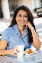 Hispanic woman sitting at sidewalk cafe Stock Images
