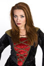 Hispanic woman wearing a costume dress red headed style velvet and staring with serious look toward the camera Royalty Free Stock Photos