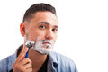 Hispanic young man shaving his beard looking at the camera as if it was a mirror and using a razor to shave on a white background Stock Photography