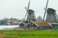 Historic Dutch village with old windmills and river landscape Royalty Free Stock Photo