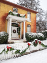 Historic home with christmas decorations brick pillared porch and and fresh snow in jacksonville oregon Royalty Free Stock Photo