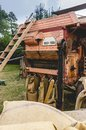 Historic threshing machine in operation. On this page, the threshed grain is filled into jute sacks. In the foreground filled Royalty Free Stock Photo