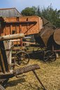 Historic threshing machine with subsequent straw press in operation. In the foreground is a historic wooden cart for the mown Royalty Free Stock Photo