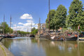 Historical gouda in holland boats and windmill on a canal the dutch town Royalty Free Stock Images