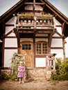 Historical house and girl an old with a young standing in front of it Royalty Free Stock Image