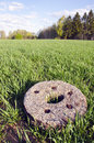 Historical millstone in the crop field Royalty Free Stock Photo