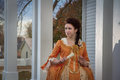 A historical woman young in clothing in front of th century mansion Royalty Free Stock Image
