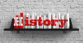 History education concept red inscription on the books on shelf on the white brick wall background Stock Photos