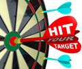 Hit your target dart on dartboard achieve success a red with the words makes a direct bulls eye in the center of a to win the game Stock Image
