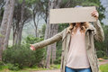Hitch hiking woman holding cardboard Royalty Free Stock Photo