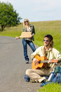 Hitch-hiking young couple backpack asphalt road Royalty Free Stock Images