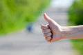 Hitchhikers sign thumb up at road background on summer day Royalty Free Stock Image