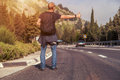 Hitchhiking traveler on the road try to stop car mountain Royalty Free Stock Images