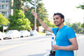 Hitchhiking or waving closeup portrait young man in blue shirt carrying water bottle and black bag raising hand to hitchhike flag Stock Photos