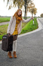 Hitchhiking young woman with thumb up Stock Images
