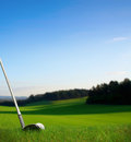 Hitting golf ball with club towards green Royalty Free Stock Photo
